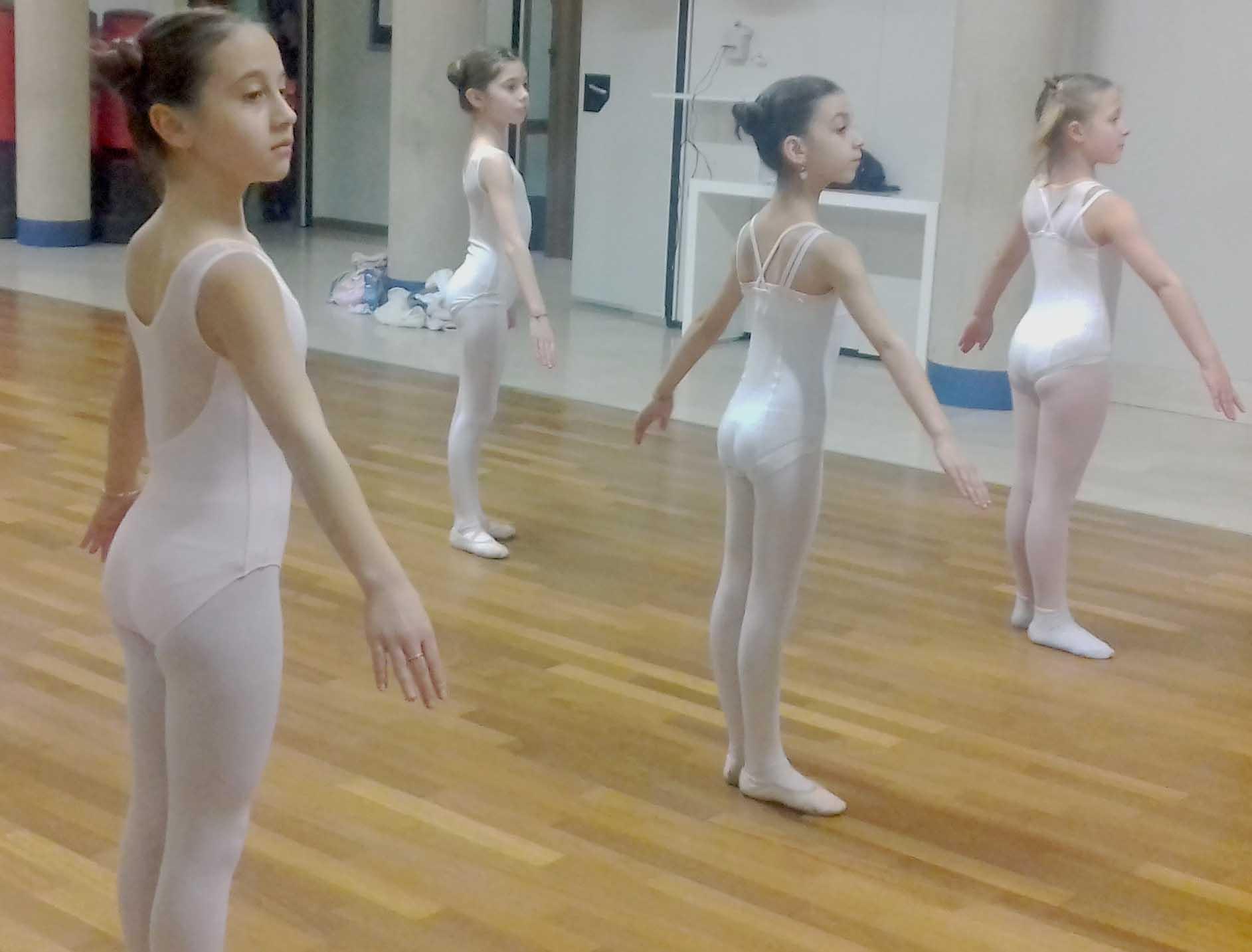 """Il corso di sbarra a terra permette agli allievi di imparare ad eseguire nella maniera corretta tutti gli esercizi che verranno eseguiti alla sbarra senza l'aggravio del peso del corpo e della forza di gravita'; impareranno ad abituare i muscoli a lavorare nella corretta direzione """"en dehors"""", necessaria per lo studio della danza classica, e ad allineare il corpo con l'ausilio del pavimento. Si incrementano gli esercizi di streatching e di flessibilità/rafforzamento muscolare della schiena. Detto corso mira a migliorare, perciò, la struttura muscolare, tendinea e la postura sia di futuri ballerini di danza classica che ballerini di danza moderna ed è per questo che è vivamente consigliato come percorso propedeutico, appunto, alle classi successive sia di classico che di moderno."""